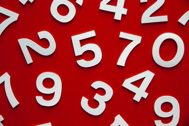 Mathematikhintergrund mit soliden zahlen auf einem brett. ansicht von oben, isoliert auf rot