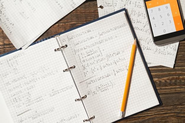 Mathematische gleichungen werden in ein notizbuch geschrieben