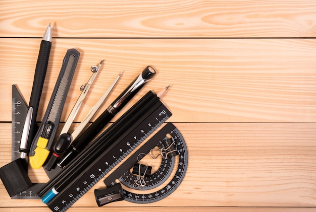 Mathematische instrumente über der ecke der hölzernen schreibtischtabelle mit kopienraum.