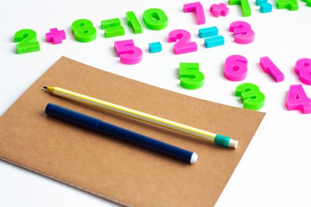 Mathematische übungen, notizbuch, kugelschreiber und bleistift