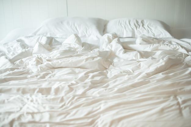 Matratzendecke und kissen auf dem luxusbett im hotelzimmer nach einem erholsamen schlaf.