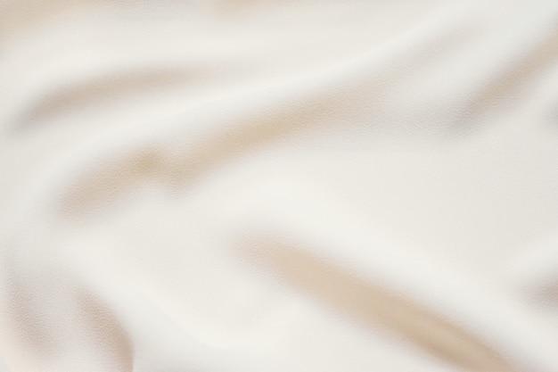 Matt cremefarbener weicher gefalteter gewebehintergrund