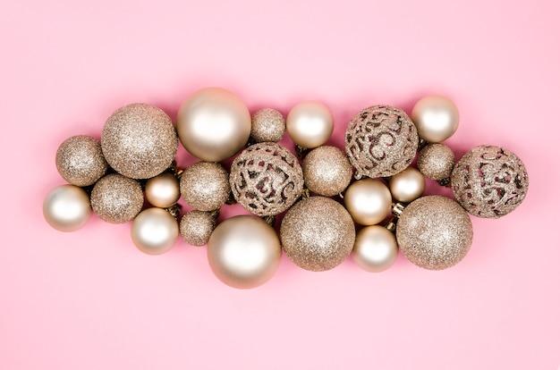 Matte goldkugeln der weihnachtskomposition und weihnachtsdekorationen auf einem rosa hintergrund