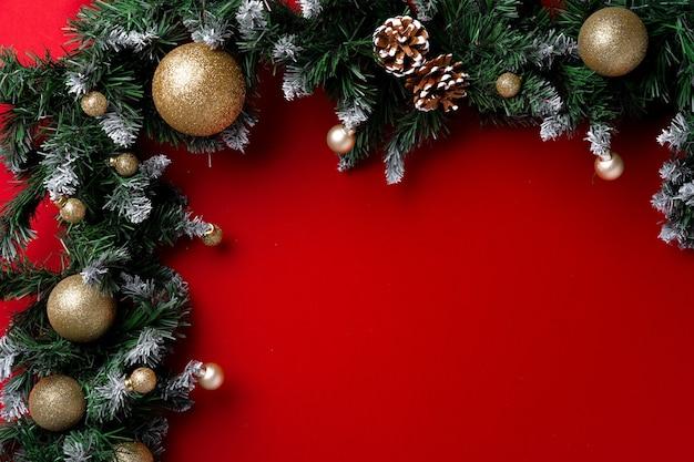 Mattierte weihnachtsbaumzweige auf roter hintergrundoberansicht