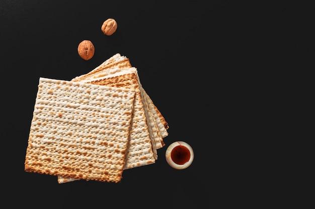 Matzah oder matza stücke auf schwarz. matzah für die jüdischen passahfeiertage.