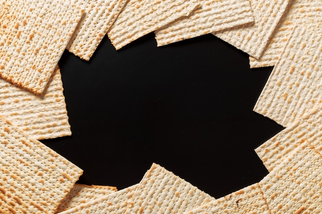 Matzah oder matzo stücke auf schwarz. matzah für die jüdischen passahfeiertage.