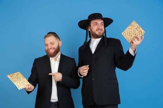 Matze essen, einladend. porträt eines jungen orthodoxen jüdischen mannes lokalisiert auf blauer wand. purim, geschäft, festival, urlaub, feier pessach oder pessach, judentum, religionskonzept.