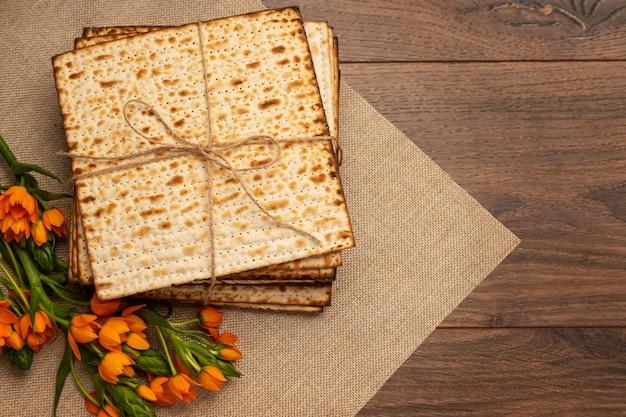 Matzo und orange blumen auf einer leinwand serviette. holzhintergrund. pessach (pesach) seder pesah feierkonzept (jüdischer pessachfeiertag). top vew