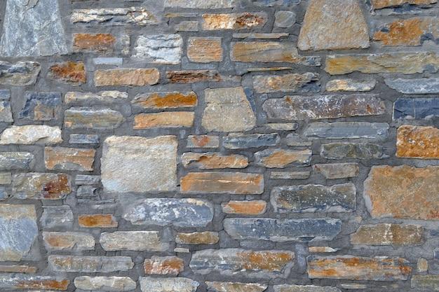 Mauer aus unebenen felssteinen an den häusern des pelionberges