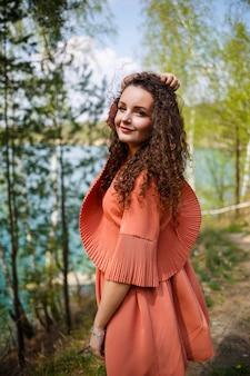 Mauerwerk aus holz. ein mädchen mit langen lockigen haaren in einem orangefarbenen guipure-kleid und schuhen in der natur, in einem wald am see, stand in der nähe von bäumen und büschen. junge frau lächelt und genießt das leben