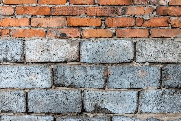 Mauerwerk aus roten lehmziegeln über grauem schaumbeton