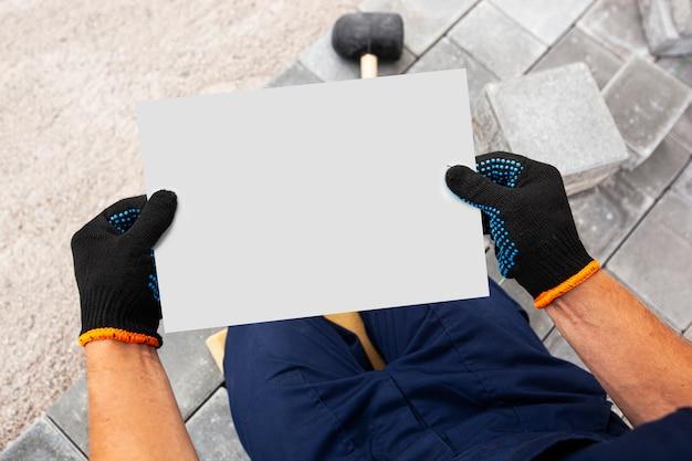 Maurer, der das weiße blatt papier mit handschuhen in der hand hält. mockup für hausreparatur oder bau