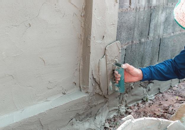 Maurer, der den beton verputzt, um eine wand zu bauen, bau