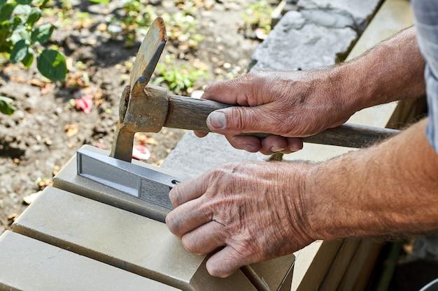 Maurer, der mit hammer und gebäudeebene ziegel auf dem neuen zaun von gegenüberliegenden ziegeln installiert