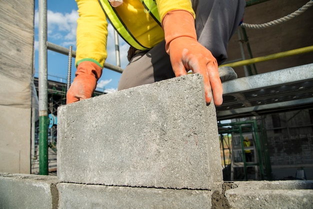 Maurerarbeitarbeiter in der standardsicherheitsuniform installieren betonblock