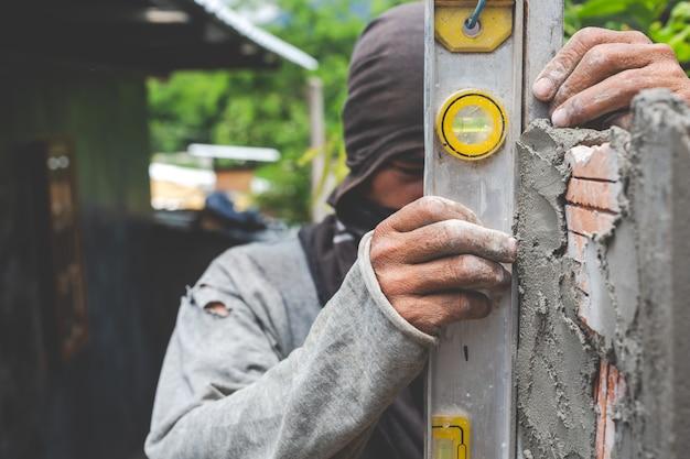 Maurerarbeiten. bauarbeiter, der eine backsteinmauer errichtet.