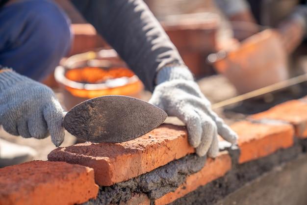 Maurerindustriearbeiter, der ziegelsteinmauerwerk mit kellenkittmesser an der baustelle installiert