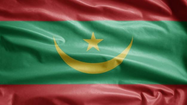 Mauretanische flagge weht im wind. mauretanisches banner weht, weiche und glatte seide. stoff stoff textur fähnrich hintergrund