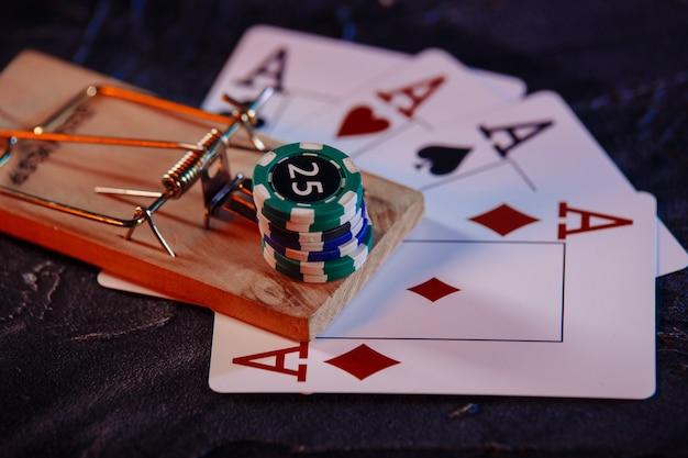 Mausefalle auf spielkarten und casino-chips in nahaufnahme. spielsucht-konzept