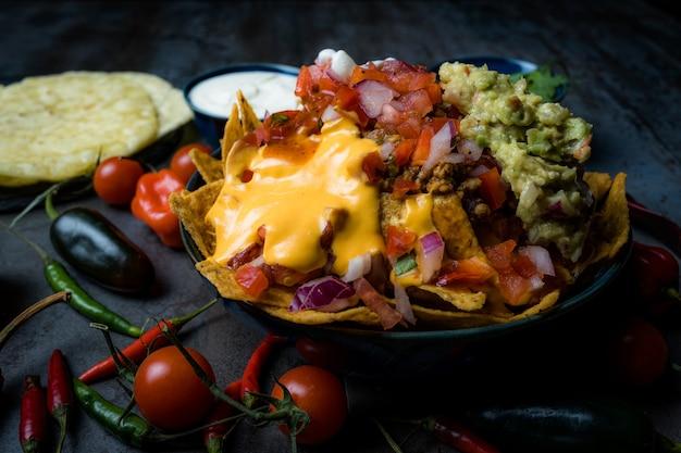 Maxican food nachos mit käse und guacamole und pico de gallo sauerrahm und tomatenkirsche