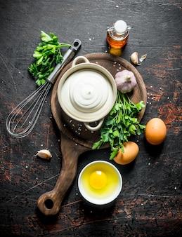 Mayonnaise auf einem schneidebrett mit petersilie, eiern und knoblauch. auf dunkel rustikal