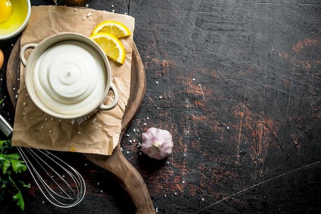 Mayonnaise in einer schüssel auf papier mit zitronen- und knoblauchscheiben.