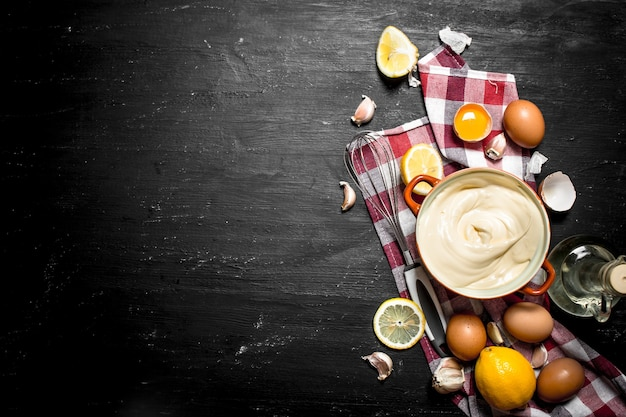 Mayonnaise mit eiern, knoblauch und zitronenscheiben auf einer schwarzen tafel