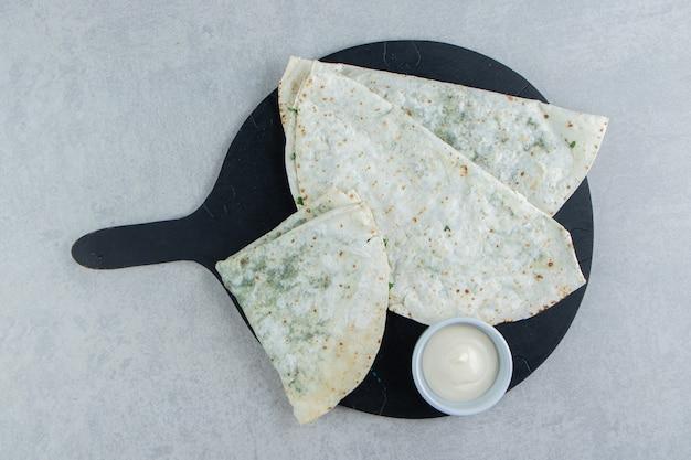 Mayonnaise und gutabs auf dem tablett, auf dem marmorhintergrund.