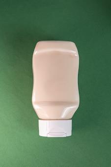 Mayonnaisebehälter auf der grünen oberfläche