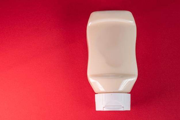 Mayonnaisebehälter auf der roten oberfläche