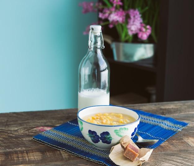 Mazamorra tasse mit guavensandwich und milchflasche auf einem rustikalen holzboden