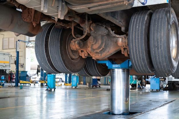 Mechaniker arbeitet mit hinterachsuntersetzungsgetriebe der lkw-wartungswerkstatt-tankstelle