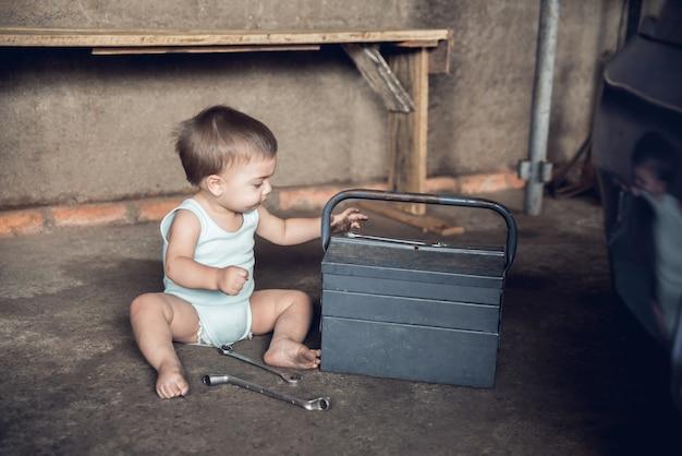 Mechaniker-baby - sitzend auf dem boden eines shops