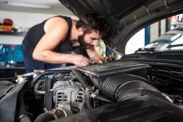 Mechaniker bei der arbeit am automotor in einer werkstatt