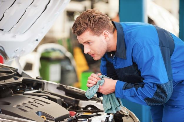 Mechaniker bei der arbeit. konzentrierter junger mann in uniform, der auto untersucht und sich die hände mit lappen abwischt, während er in der werkstatt steht