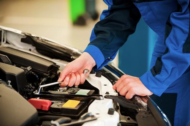 Mechaniker bei der arbeit. nahaufnahme eines mannes in uniform, der auto repariert, während er in der werkstatt steht
