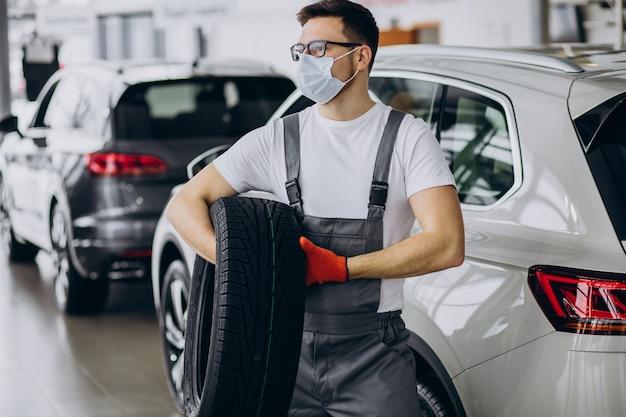 Mechaniker beim reifenwechsel in einem autoservice