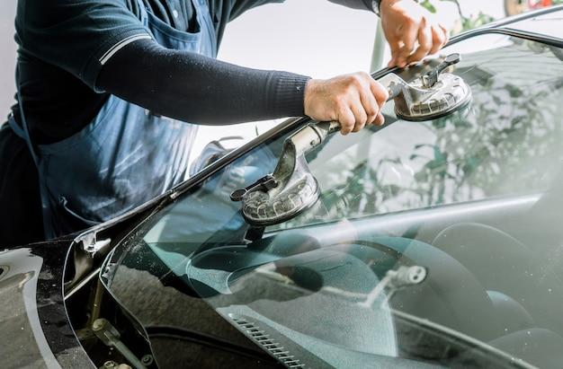 Mechaniker bemannen das ändern der defekten windschutzscheibe und der automobilwindschutzscheibe oder des windschutzscheibenersatzes des weißen autos in der autowerkstatt