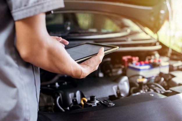 Mechaniker benutzt eine tablette, um den motor zu überprüfen