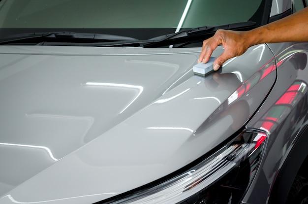 Mechaniker beschichtet keramikglas, um kratzer auf autos zu vermeiden.