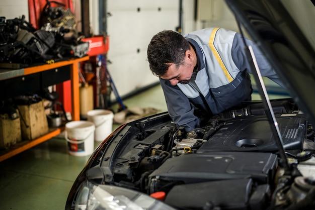 Mechaniker, der an einem fahrzeug in der werkstatt arbeitet.