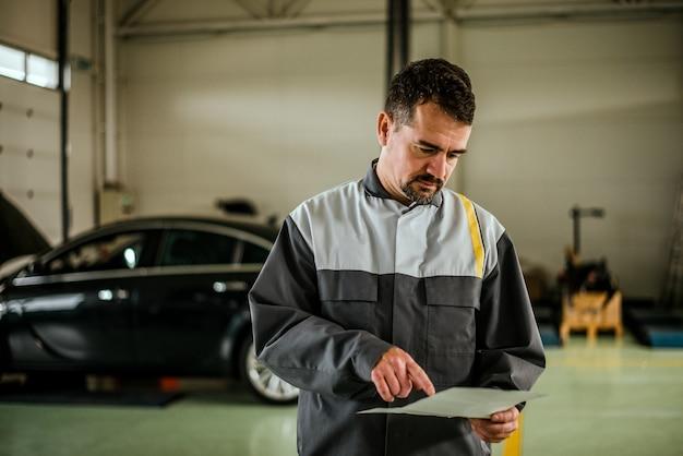 Mechaniker, der anmerkungen bei der stellung in der garage betrachtet.