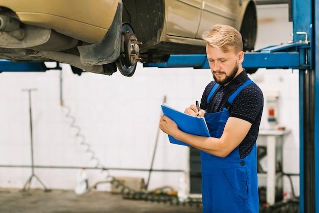 Mechaniker, der auto in der werkstatt überprüft