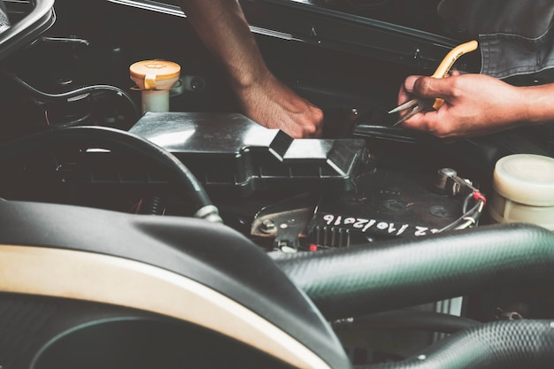 Mechaniker, der auto repariert und den motor täglich vor gebrauch überprüft.
