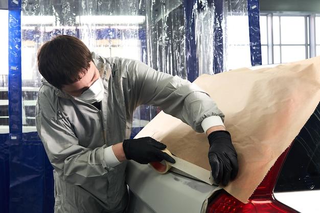 Mechaniker, der auto vor dem lackieren im autoreparaturservice mit papier abdeckt