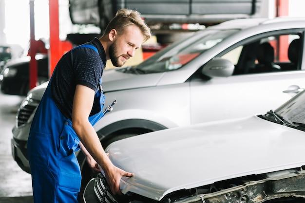 Mechaniker, der autohaube öffnet