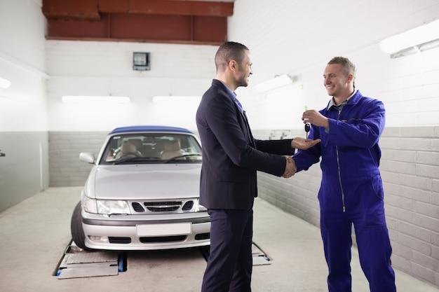 Mechaniker, der autoschlüssel beim rütteln der hand zu einem kunden gibt
