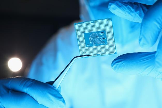 Mechaniker, der computerprozessor mit pinzette in labornahaufnahme hält
