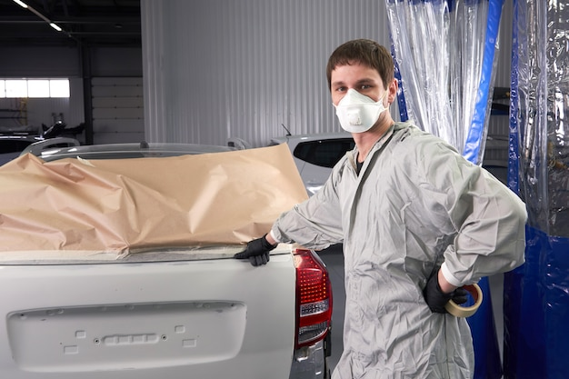 Mechaniker, der das auto vor dem lackieren im autoreparaturservice abdeckt
