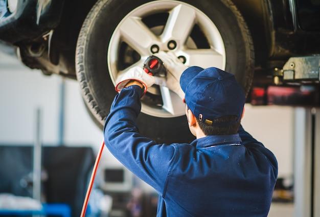 Mechaniker, der das autorad in der autowerkstatt wechselt